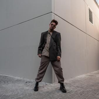 Knappe modieuze man model in stijlvol grijs pak met fashion zonnebril staat in de buurt van modern gebouw in de stad