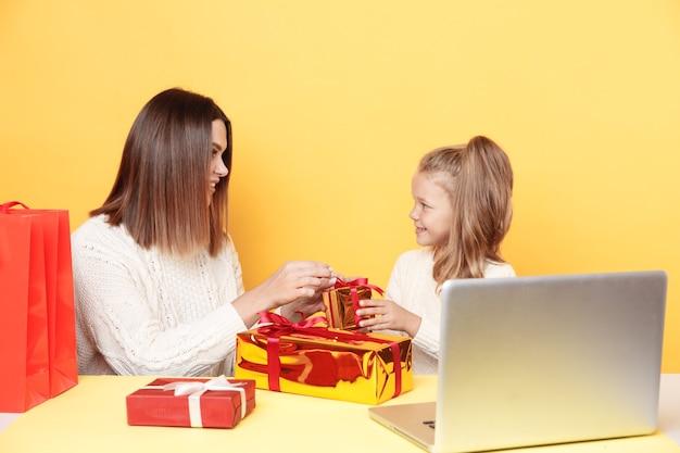 Knappe moeder met dochtertje geschenken zittend geïsoleerd op geel losmaken
