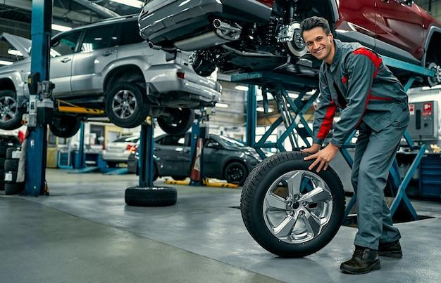Knappe monteur in uniform werkt in de autoservice. auto reparatie en onderhoud. autowiel vasthouden.