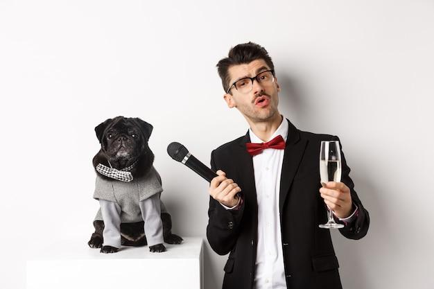 Knappe mooie man in glazen, glas champagne verhogen en microfoon geven aan schattige mopshond in feestpak, vieren en plezier hebben, witte achtergrond