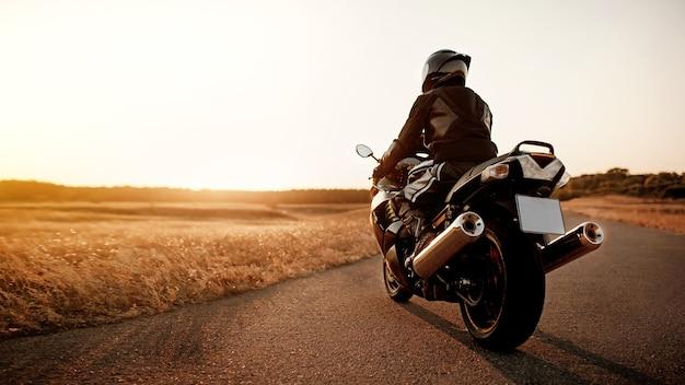 Knappe motorrijder in leren jas en helm bij zonsondergang op de weg in warme zonnestralen