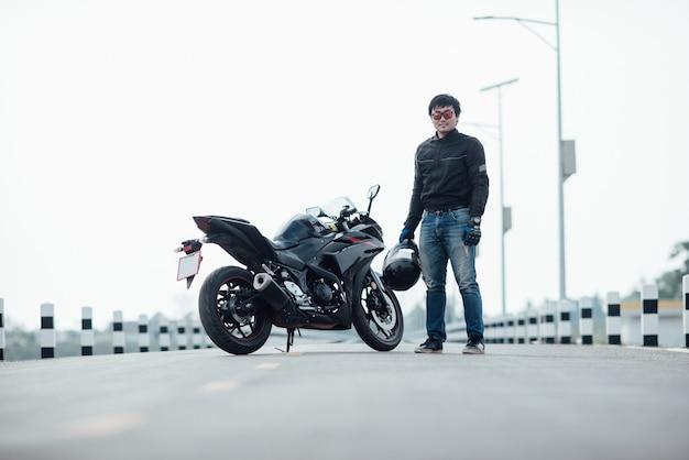 Knappe motorrijder met helm in handen van motorfiets