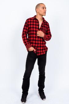 Knappe multi-etnische kale hipster man met rood geruit overhemd tegen een witte muur