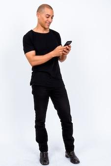 Knappe multi-etnische kale man met zwarte shirt tegen een witte muur