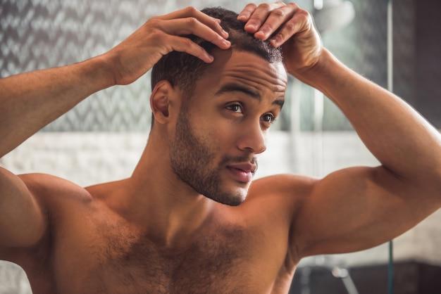 Knappe naakte afro-amerikaanse man onderzoekt zijn haar.