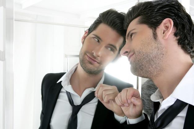Knappe narcistische jonge man op zoek in een spiegel