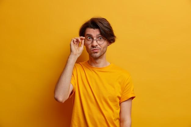 Knappe nieuwsgierige man kijkt aandachtig door een bril, heeft een aandachtige blik, gekleed in vrijetijdskleding, heeft een nauwgezette blik, geïsoleerd op een gele muur, krijgt een interessante suggestie