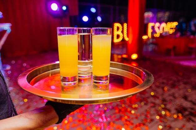 Knappe ober met blote handen dienblad met glazen vol cocktail nachtfeest in club