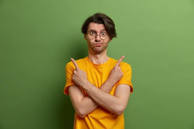 Knappe onbewuste volwassen man aarzelt tussen twee goede keuzes, wijst zijwaarts, kruist handen over de borst, geeft links en rechts aan, kan niet kiezen wat hij wil kiezen, gekleed in een levendig geel t-shirt