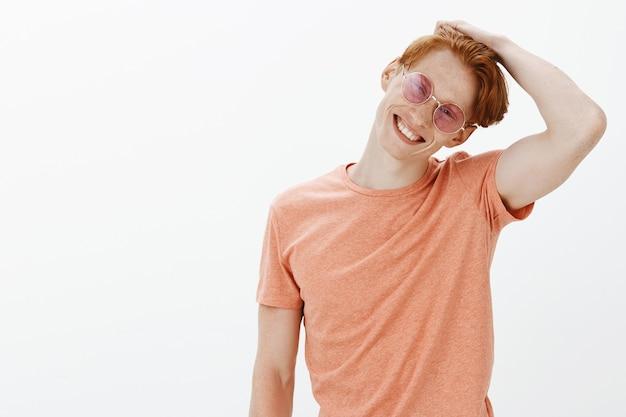 Knappe onbezorgde roodharige man geniet van de zomer, draagt een zonnebril en lacht