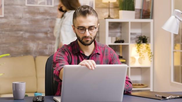 Knappe ondernemer die een slokje koffie neemt terwijl hij op een laptop in de woonkamer werkt. vriendin op de achtergrond praat aan de telefoon.
