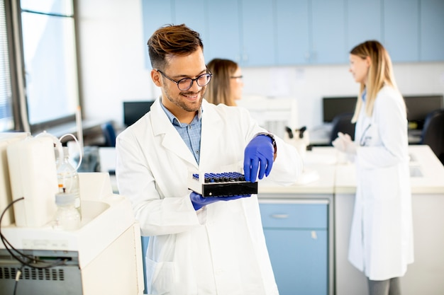 Knappe onderzoeker in beschermende werkkleding die in het laboratorium staat en vloeibare monsters analyseert