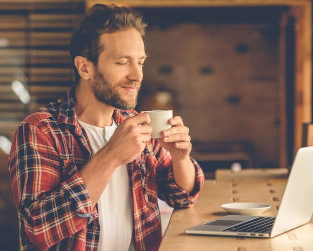 Knappe ontwerper geniet van het aroma van koffie.