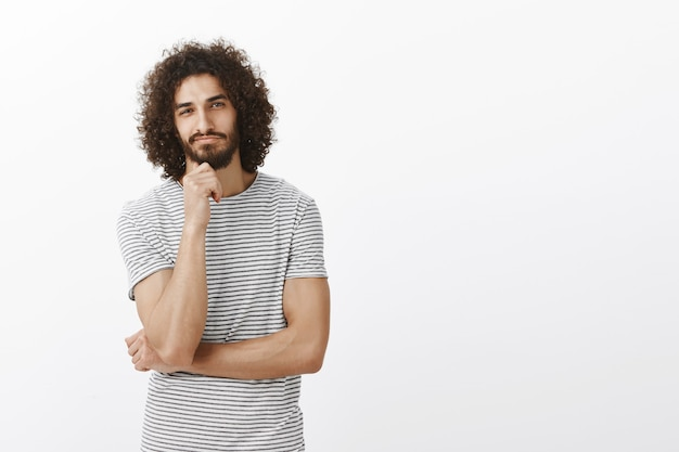 Knappe oosterse mannelijke collega in trendy gestreept t-shirt, hoofd op vuist leunend terwijl staande met half gekruiste vingers