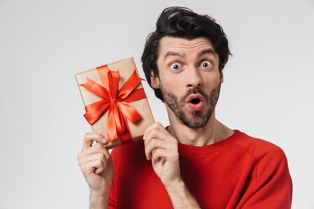 Knappe opgewonden jonge bebaarde brunette man met trui permanent over wit, huidige doos te houden