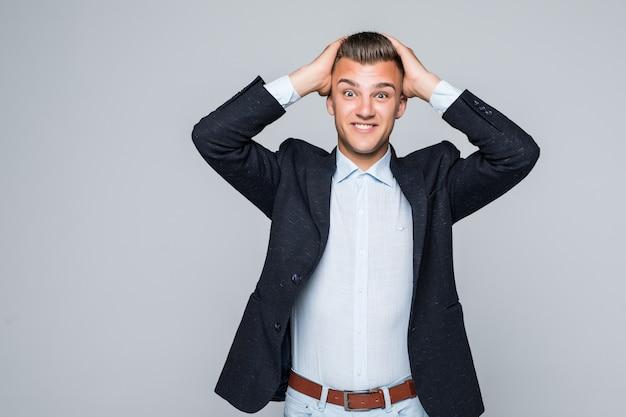 Knappe opgewonden jonge man in shirt en spijkerbroek houdt zijn armen op zijn hoofd