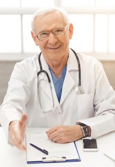 Knappe oude arts in witte medische jas en bril.