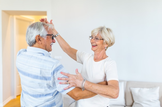 Knappe oude man en aantrekkelijke oude vrouw genieten van tijd samen doorbrengen tijdens het dansen