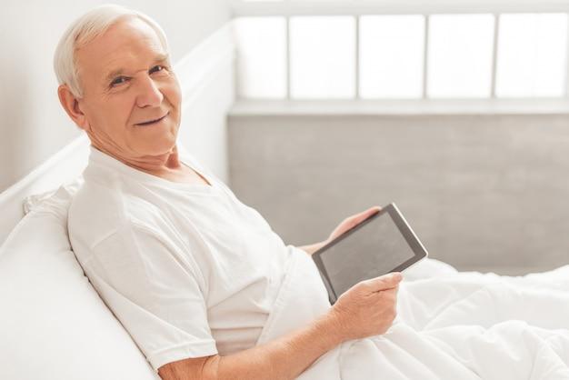 Knappe oude man gebruikt een digitale tablet.