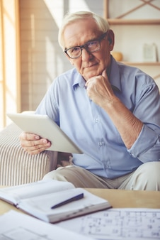Knappe oude man in bril gebruikt een digitale tablet.