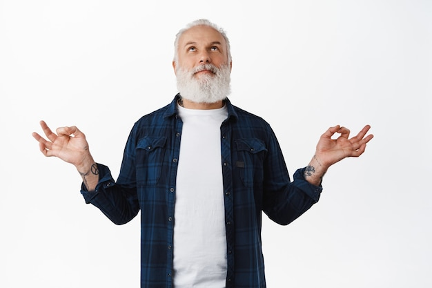 Knappe oude man met tatoeages mediterend, glimlachend terwijl hij omhoog kijkt en een zen mudra-gebaar maakt, yoga beoefent, vredig ademt, ontspannende geest, staande over een witte muur