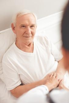 Knappe oude patiënt praat met zijn arts