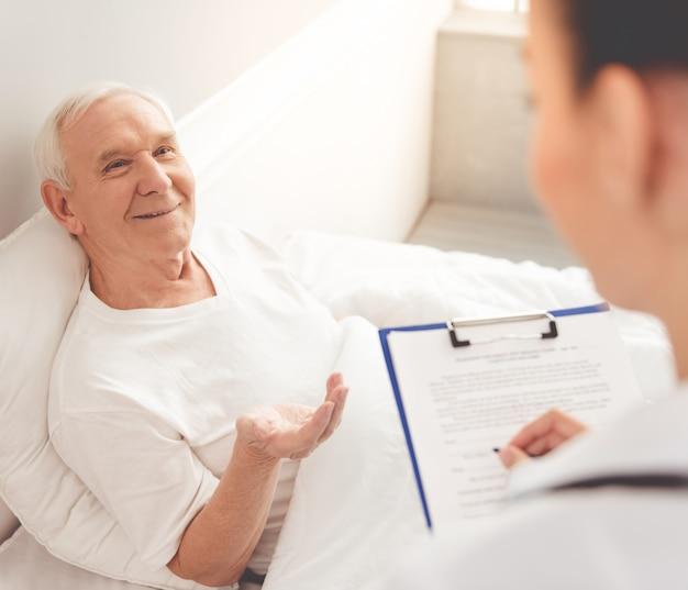 Knappe oude patiënt praat met zijn arts.