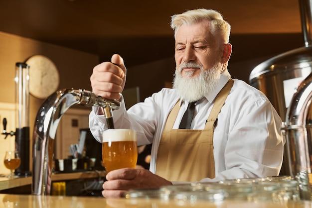 Knappe, oudere barman bij toog licht bier gieten. bebaarde man in wit overhemd en bruine schort met koud glas pils met schuim. concept van brouwerij en handel.