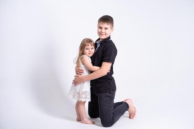 Knappe oudere broer tiener knuffelen zijn schattige kleine zusje op witte achtergrond.