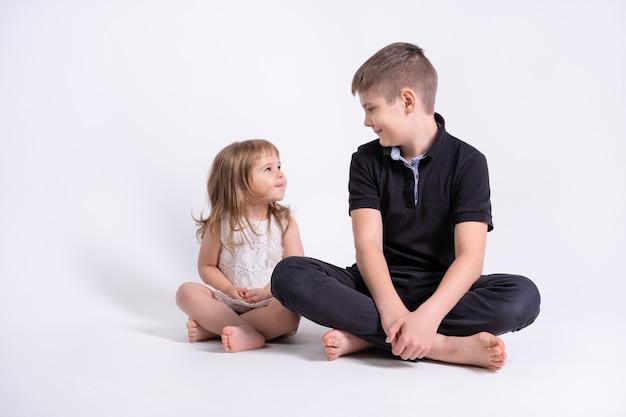 Knappe oudere broer tiener zit samen met zijn schattige kleine zusje op witte achtergrond.