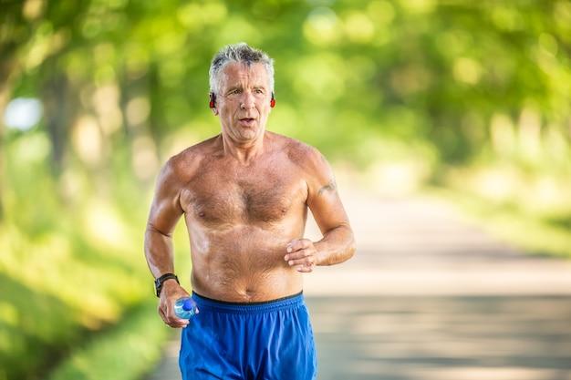 Knappe oudere man rent topless buiten in de natuur om in vorm te blijven.