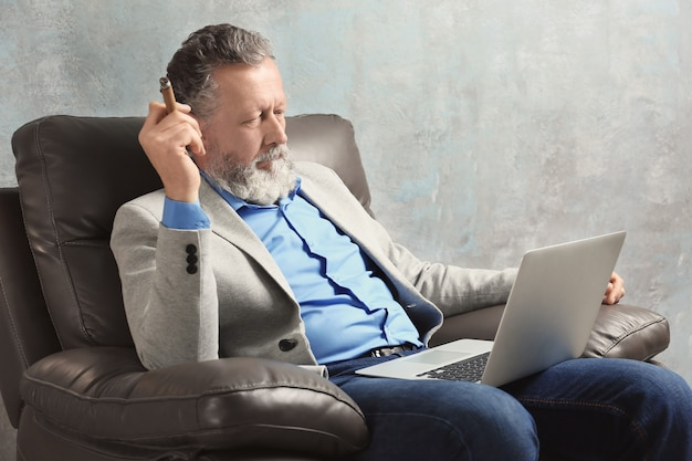Knappe oudere man zit in fauteuil met laptop