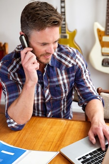 Knappe oudere mens op oproep bij muziekstudio
