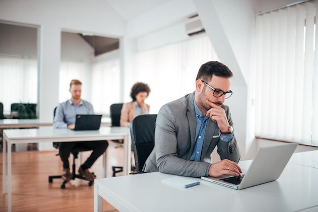 Knappe peinzende zakenman die aan laptop in coworking bureau werkt.