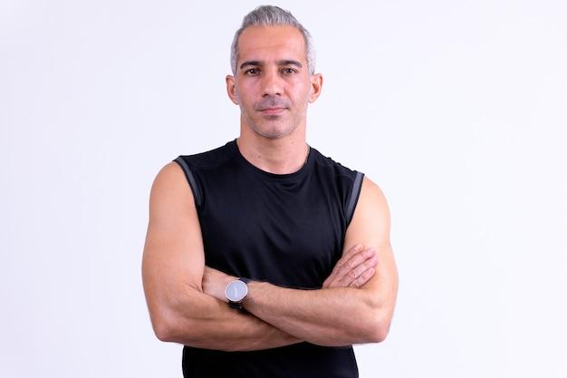 Knappe perzische man met gekruiste armen klaar voor sportschool tegen whi