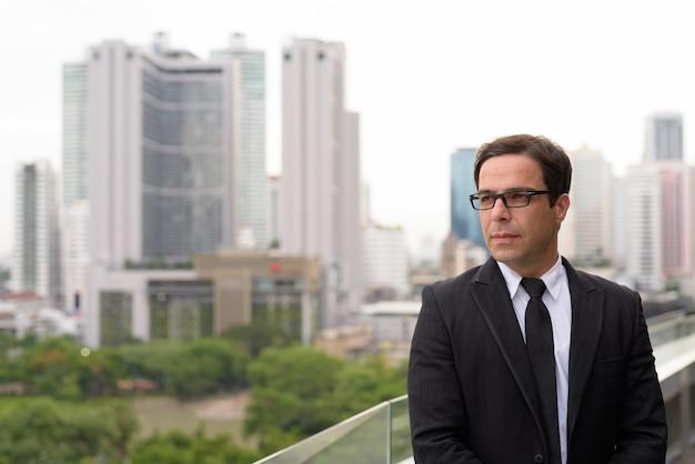 Knappe perzische zakenman tegen mening van de stad