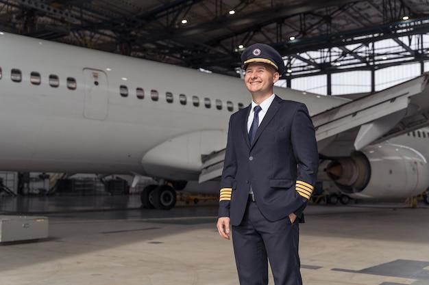 Knappe piloot poseert tegen de achtergrond van het vliegtuig in de hangar