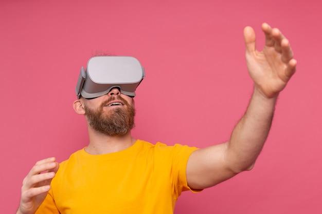 Knappe positieve bebaarde man aanraken van lucht op vr-bril studio achtergrond Gratis Foto