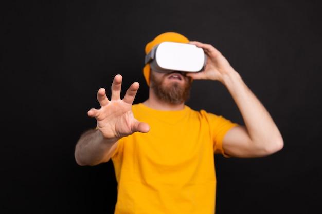 Knappe positieve bebaarde man aanraken van lucht op vr-bril studio achtergrond
