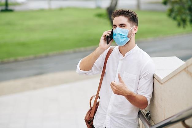 Knappe positieve jonge man in medisch masker praten aan de telefoon met collega of vriend