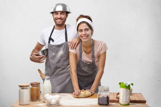 Knappe positieve jonge vrouw die hoofdband en schort draagt die deeg voor pizza of lasagne kneedt met blije glimlach