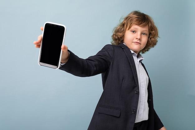 Knappe positieve jongen met krullend haar in pak met telefoon geïsoleerd over blauwe achtergrond kijkend naar camera en smartphone met leeg scherm tonend