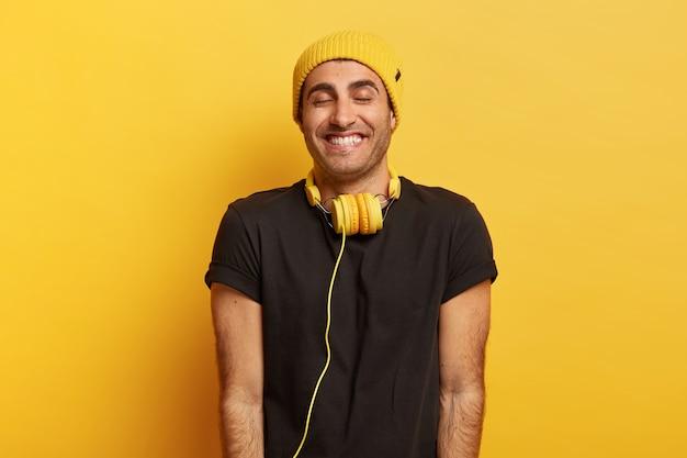 Knappe positieve man met koptelefoon op nek, breed glimlacht en ogen sluit van plezier, draagt hoed en zwart t-shirt