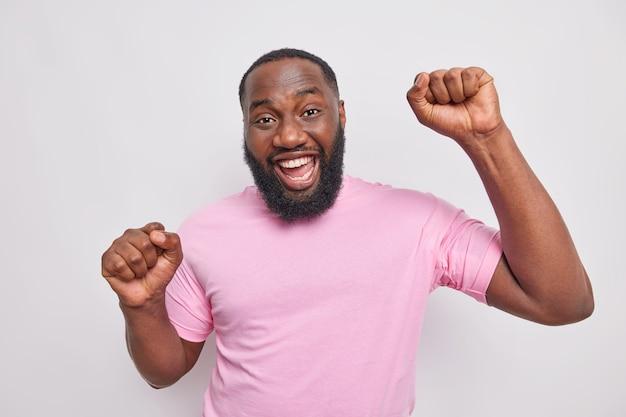 Knappe positieve ongeschoren man maakt triomfdans heft vuisten heeft plezier op feest drukt blije emoties glimlacht breed draagt casual roze t-shirt geïsoleerd over grijze muur