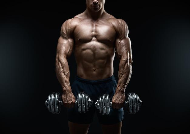 Knappe power atletische man bodybuilder doen oefeningen met halter. fitness gespierd lichaam op donkere achtergrond.