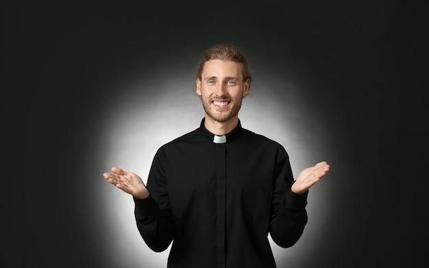 Knappe priester op donkere achtergrond