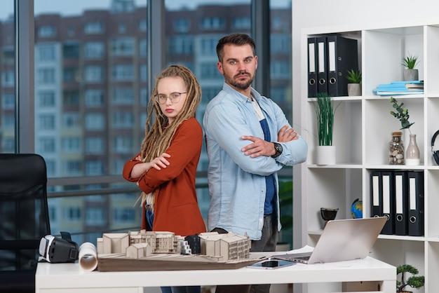 Knappe professionele architect staat rijtjes met mooie vrouwelijke collega met dreadlocks op