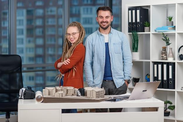 Knappe professionele jonge ingenieur staat rijtjes met mooie vrouwelijke collega met dreadlocks bij ontwerpbureau.
