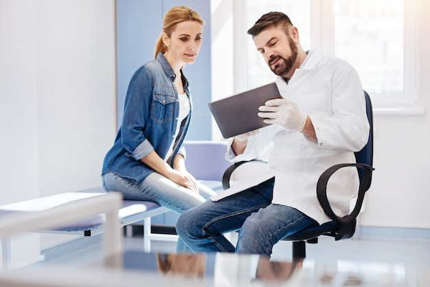 Knappe professionele mannelijke arts die een tablet vasthoudt en een foto erop toont aan zijn patiënt terwijl hij een toekomstige operatie bespreekt