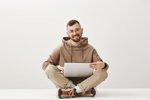 Knappe programmeur die met laptop werkt